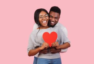 young couple in gray sweaters holding red love heart