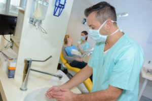 dentist in Manahawkin washing their hands before putting on gloves