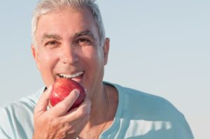 Man with dental implants in Manahawkin biting an apple.