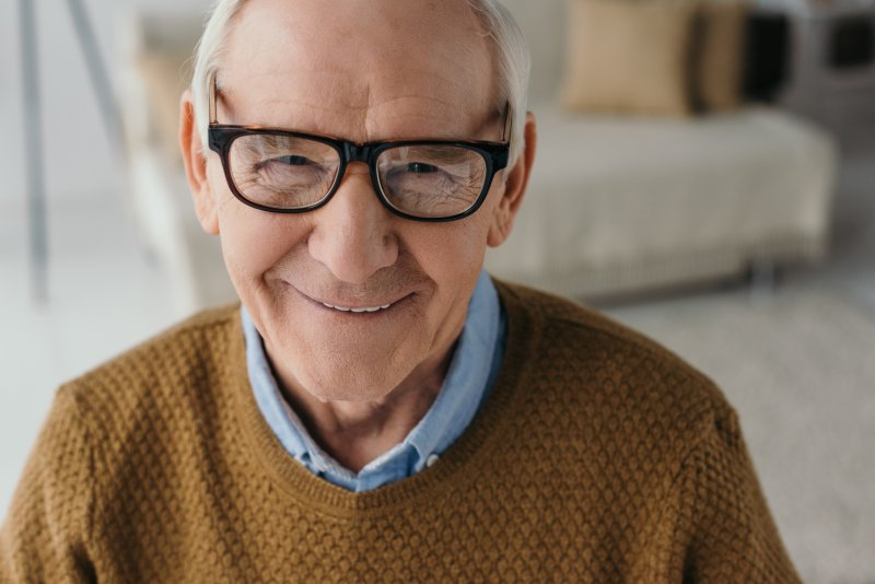 an older man wearing a brown sweater and glasses smiles after receiving his dental implants